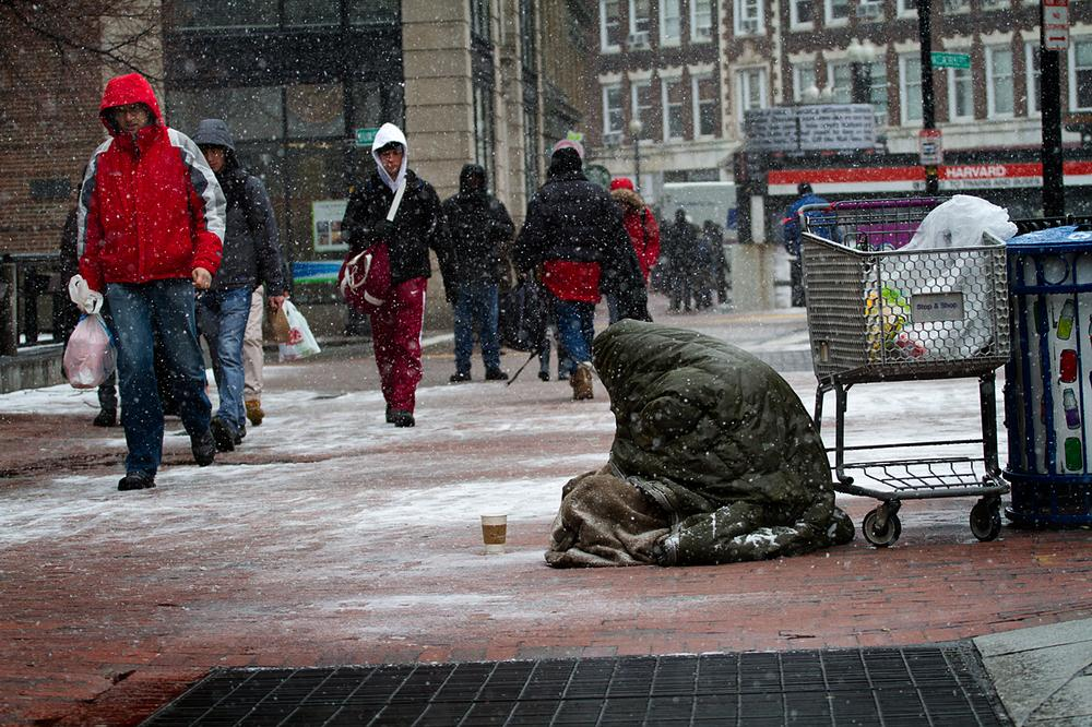 A homeless person panhandles in the snow in Harvard Square, Cambridge, Mass. on Friday, Feb. 8, 2013.(Jesse Costa/WBUR)