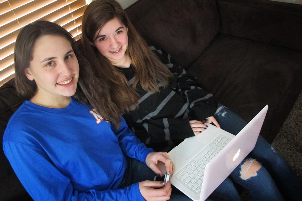 """Newton South High School sophomores Chloe Miller and Paige Herer log on to Facebook 10 to 20 times a day. They say posting and """"liking"""" profile pictures are a huge part of some teens' social media experience. (Andrea Shea/WBUR)"""