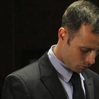 Olympic athlete Oscar Pistorius stands inside the court as a police officer looks on during his bail hearing at the magistrate court in Pretoria, South Africa, Wednesday, Feb. 20, 2013. (Themba Hadebe/AP)