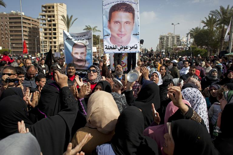 In this Friday, Feb. 22, 2013 photo, Egyptian protesters chant anti-President Mohammed Morsi slogans and carry posters with pictures of victims of recent violence and their names in Port Said, Egypt. (Nasser Nasser/AP)