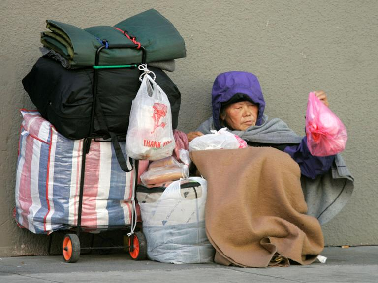 A woman huddles on a street corner in San Francisco in January 2009. (Marcio Jose Sanchez/AP)
