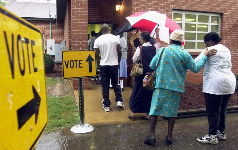 A line of voters stand in the rain outside this Montgomery, Ala., polling place as they wait to cast their ballots in the general election on Tuesday, Nov. 7, 2000. (Dave Martin/AP)