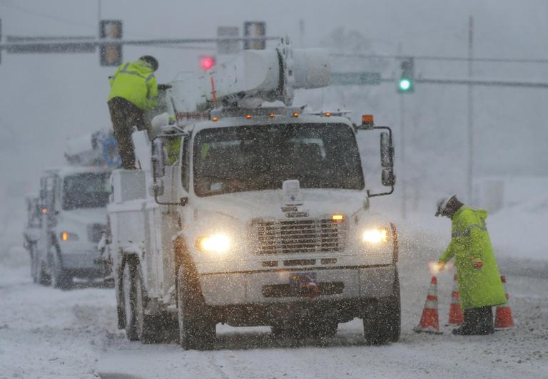 Westar Energy crews begin work on snow covered power lines in Lawrence, Kan., Tuesday, Feb. 26, 2013. (Orlin Wagner/AP)