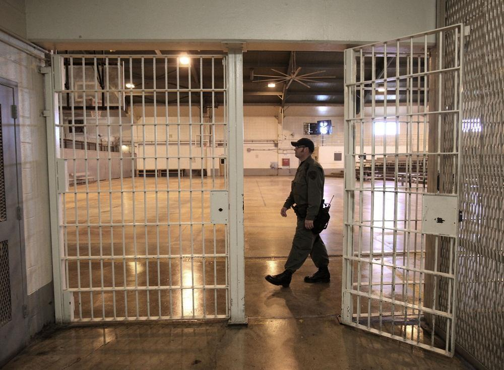 A correctional officer walks in a gymnasium that housed overflow prisoners in Tracy, California (Rich Pedroncelli/AP)