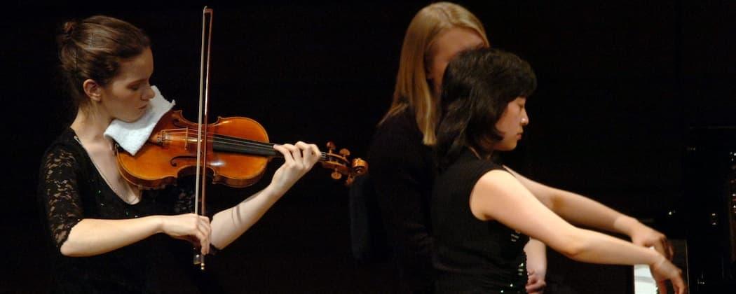 Hilary Hahn and Natalie Zhu in a 2005 concert.  (Photo courtesy of AP//Keystone/Sigi Tischler)