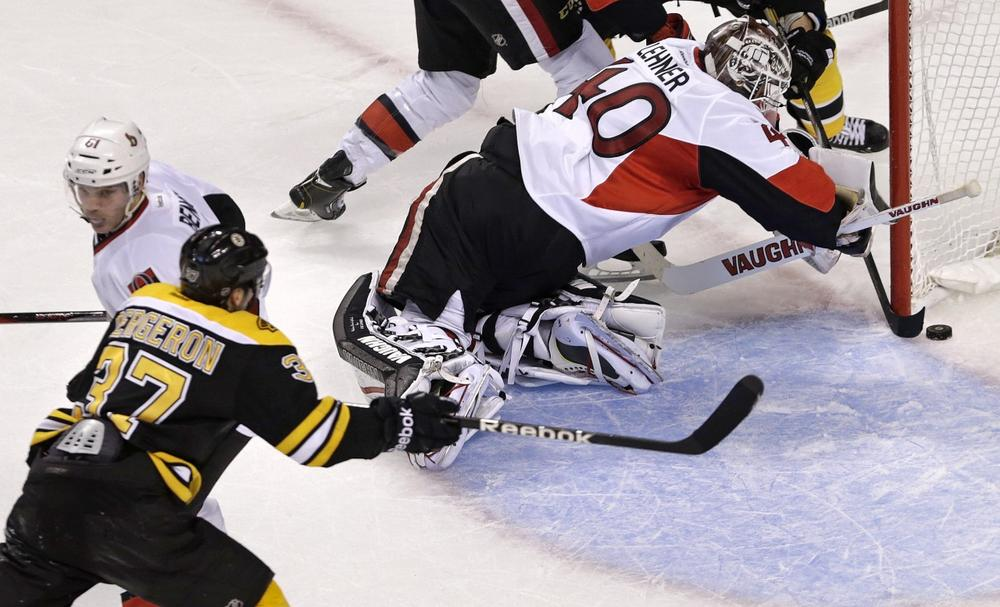 Ottawa Senators goalie Robin Lehner (40) tries to get his stick around as the puck crosses the goal line into the net on a goal by Boston Bruins center Patrice Bergeron. (Charles Krupa/AP)