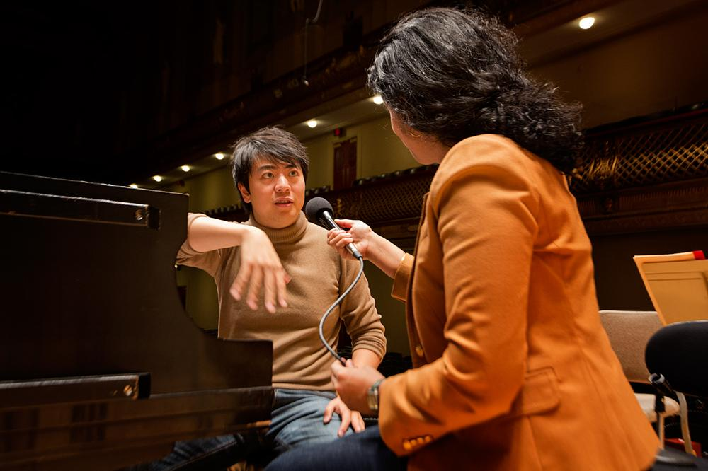 Classical pianist Lang Lang being interviewed by Meghna Charkrabarti at Boston Symphony Hall. (Jesse Costa/WBUR)