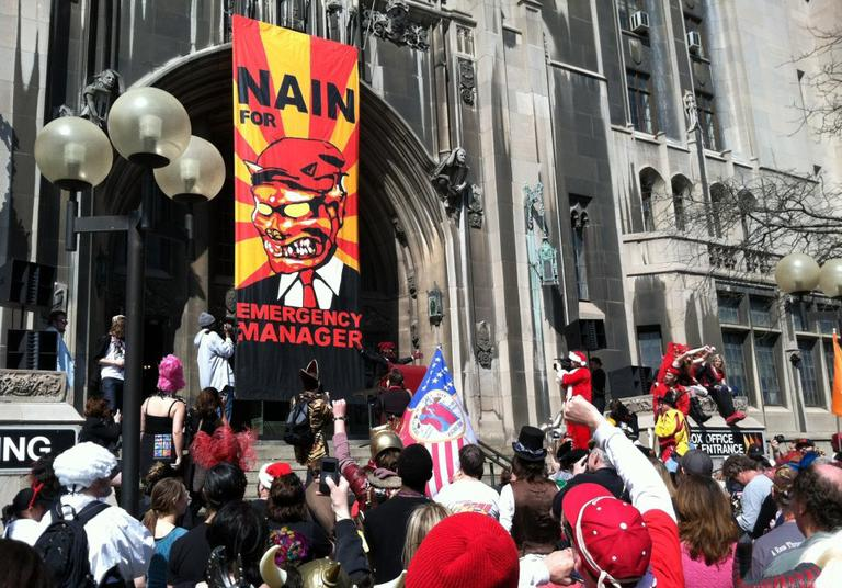 """A man dressed as Detroit's mythical """"little red devil,"""" the Nain Rouge, announces his candidacy for Detroit emergency manager at the """"Marche Du Nain Rouge""""festivitieslast year in Detroit. (Julie Phenis/Facebook)"""