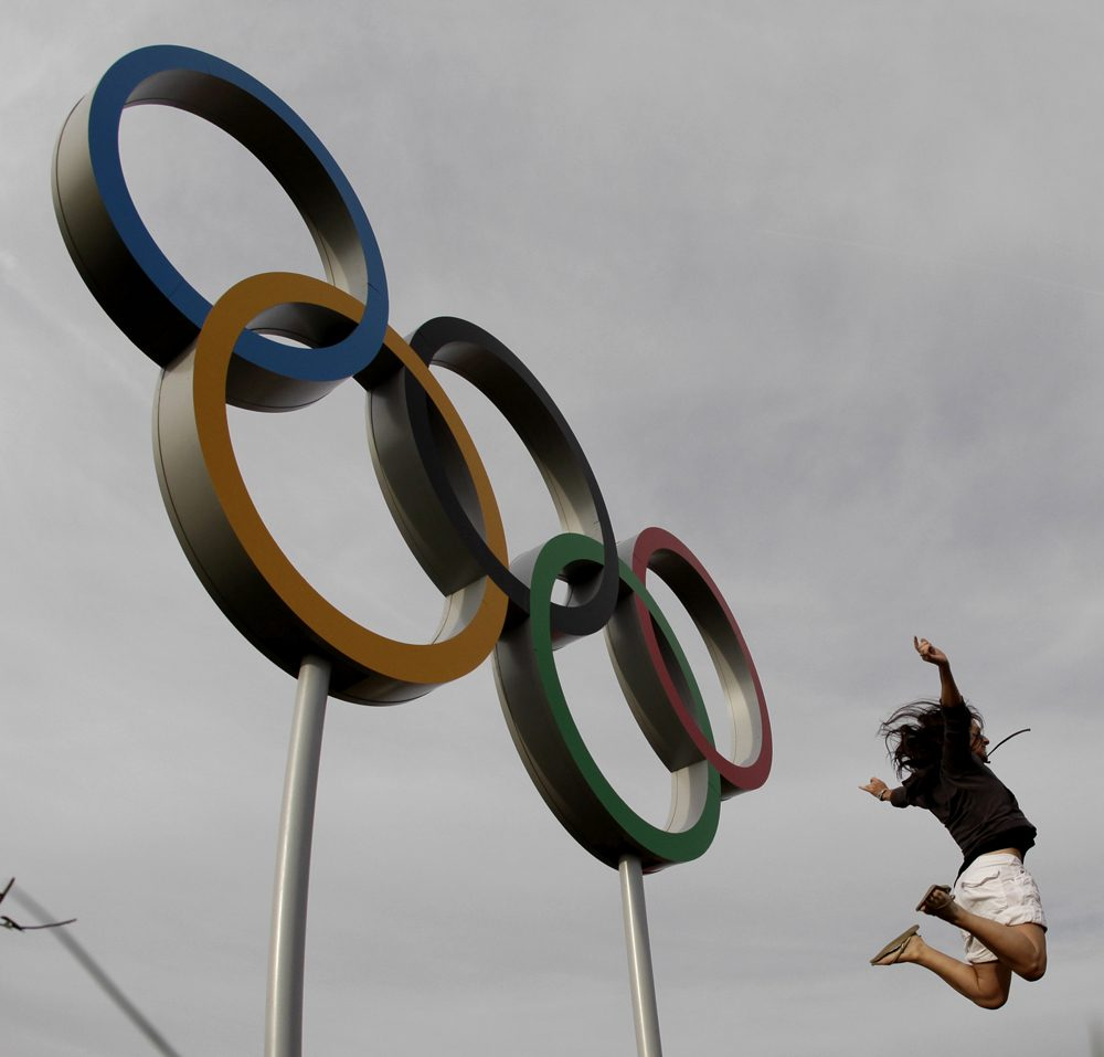 A visitor to Olympic Park jumps in the air by a set of Olympic rings at the 2012 Summer Olympics Saturday, Aug. 11, 2012, in London. (Charlie Riedel/AP)