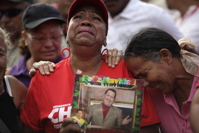 Supporters of Venezuela's President Hugo Chavez cry outside the military hospital where President Hugo Chavez, aged 58, died on Tuesday in Caracas, Venezuela, Wednesday, March 6, 2013. (Ariana Cubillos/AP)
