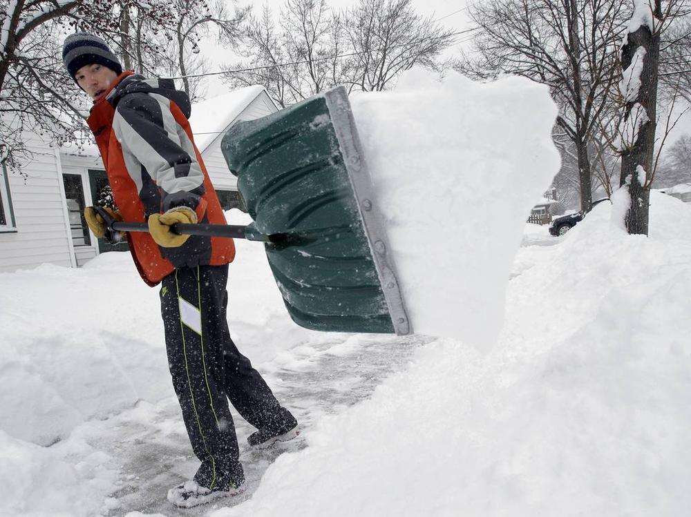 Mike Flynn of Minneapolis was out shoveling snow early Tuesday. (Jim Mone/AP)