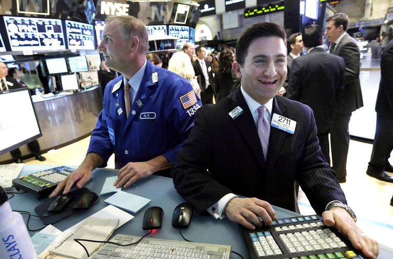 Specialist Christian Sanfillippo, right, smiles as he works at his post on the floor of the New York Stock Exchange on Tuesday, March 5, 2013. (Richard Drew/AP)