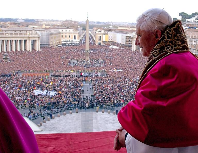 The crowd in St. Peter's Square can be seen behind Pope Benedict XVI, after he makes his first appearance, April 19, 2005 (click to enlarge). (L'Osservatore Romano/AP)