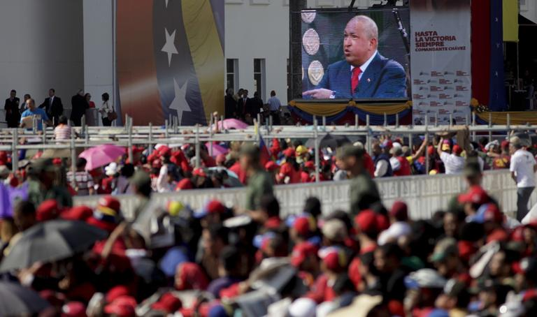 A screen showing a video image of Venezuela's President Hugo Chavez plays in front of the site where Chavez's funeral ceremony will take place as people gather outside the military academy in Caracas, Venezuela, Friday, March 8, 2013. (Ariana Cubillos/AP)