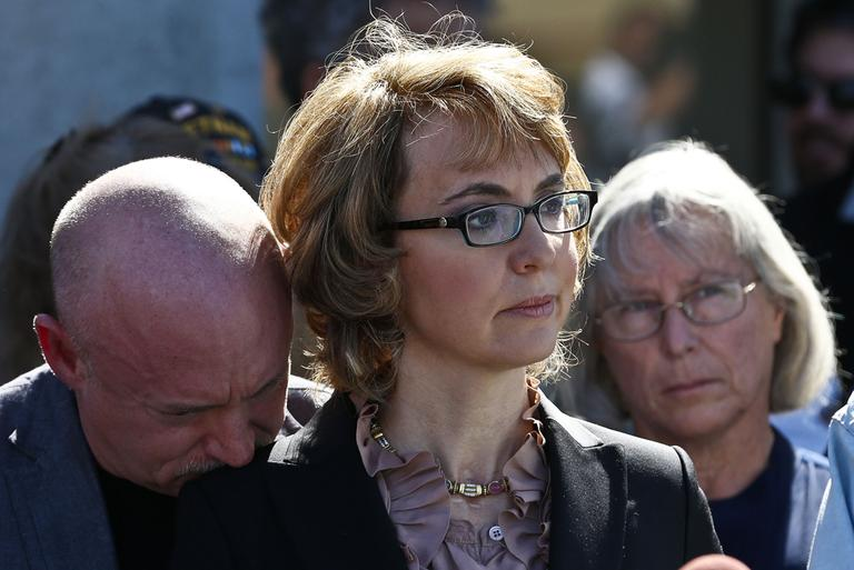 Former Rep. Gabrielle Giffords, center, is joined by her husband on Wednesday at the site of a shooting that left her critically wounded. (Ross D. Franklin/AP)