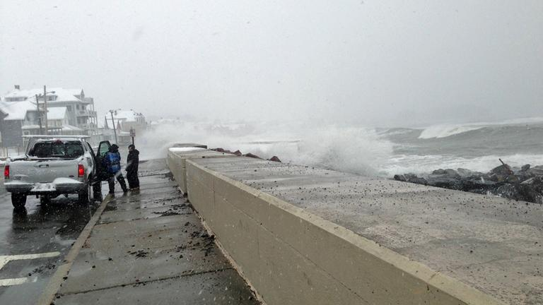 Waves breech the seawall in Winthrop Friday morning as onlookers leave before they get wet. (Jesse Costa/WBUR)