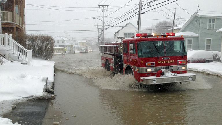 A firetruck drives down a flooded street on Shirley Point in Winthrop Friday morning. (Jesse Costa/WBUR)
