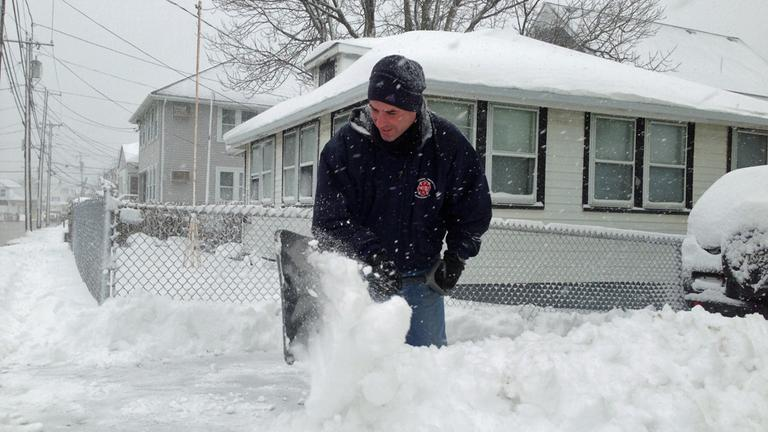 A Winthrop resident shovels snow Friday morning. (Jesse Costa/WBUR)
