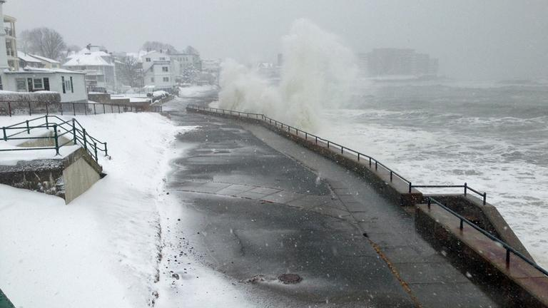 Waves crash against the seawall in Winthrop Friday morning. (Jesse Costa/WBUR)