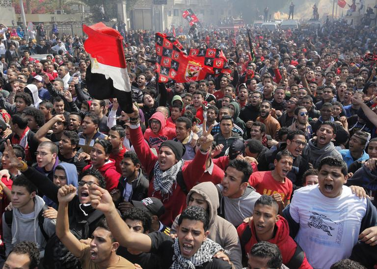 Egyptian soccer fans of Al-Ahly club wave national and Al-Ahly flags as they celebrate in front of their club headquarters in Cairo, Egypt, Saturday, March 9, 2013. (Amr Nabil/AP)