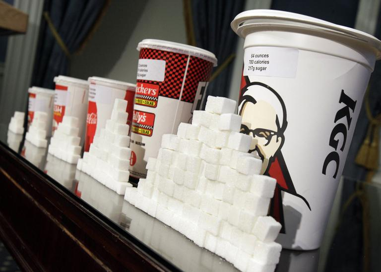 A display of various size soft drink cups next to stacks of sugar cubes at a news conference at New York's City Hall on  May 31, 2012. (Richard Drew/AP)