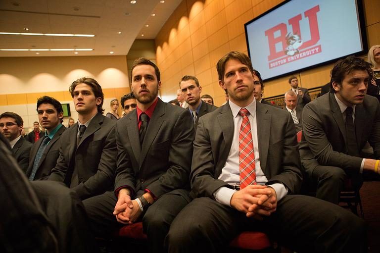 Members of the BU hockey team watch as Jack Parker announces his retirement at Agannis Arena on Monday. (Jesse Costa/WBUR)