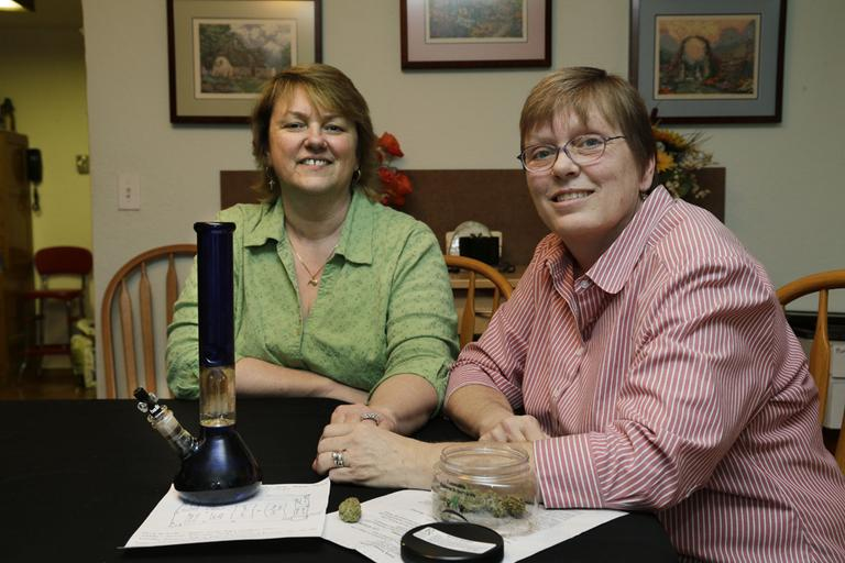 Married couple Kimberly Bliss, left, and Kim Ridgway, right, pose for a photo at their home in Lacey, Wash, in February 2013. On the table in front of them is medical marijuana and a water pipe that Ridgway uses to treat arthritis and severe anxiety. (Ted S. Warren/AP)