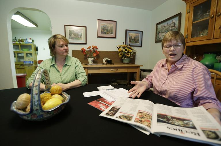 "Kimberly Bliss, left, and her wife Kim Ridgway, right, look at recipes for marijuana ""edibles"" as they sit at their dining room table in February 2013. (Ted S. Warren/AP)"