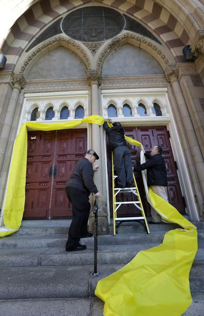 Volunteers hang papal bunting to signify the naming of a new pope, outside Cathedral of the Holy Cross, in Boston on Wednesday. (Steven Senne/AP)