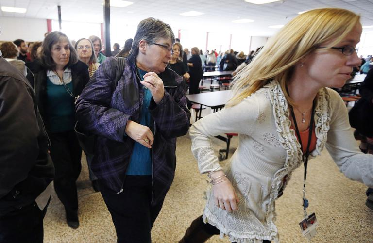 Participants rush out of the cafeteria after hearing gun shots during a lockdown exercise at Milford High School on Friday. (Michael Dwyer/AP)