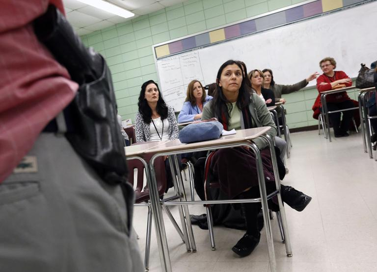 Teacher Astrid Barrios, center, listens as Milford, Mass., police detective Carlos Sousa, left, debriefs participants after a lockdown exercise at Milford High School on Friday. (Michael Dwyer/AP)