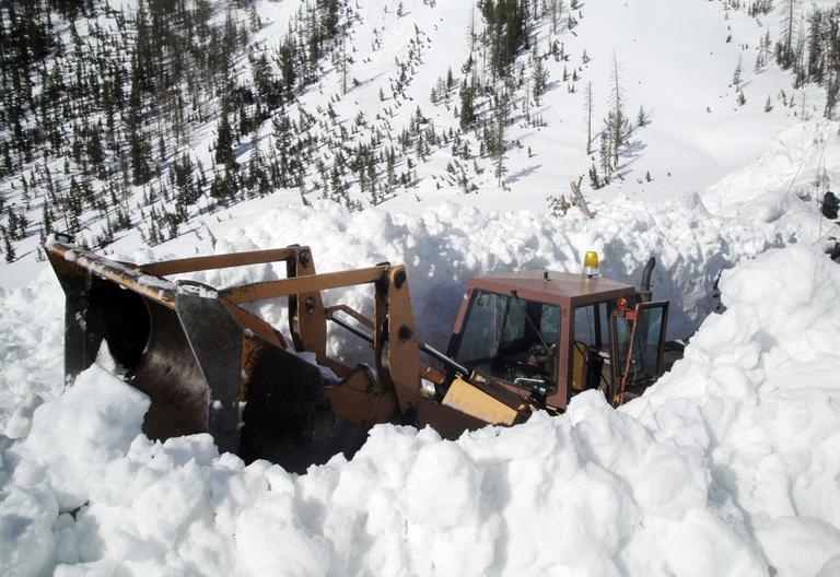 This image provided by the National Park Service shows a front loader clearing off a snow-blocked Sylvan Pass inside Yellowstone National Park May 11, 2011 in Montana. (National Park Service/AP)