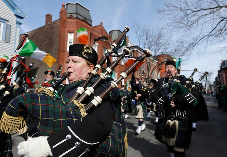 Members of the Quaboag Highlanders, of Monson, Mass., blow bagpipes while marching in the parade. (Steven Senne/AP)