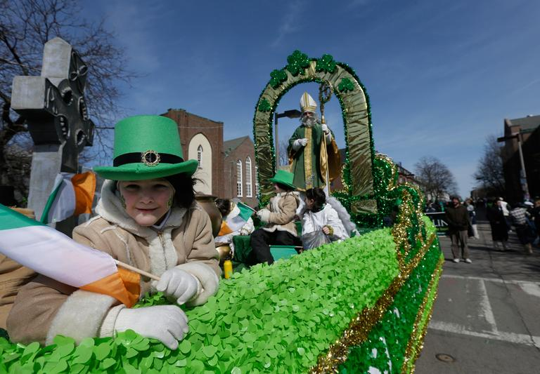 A girl holds an Irish flag while in costume on a St. Patrick's Day float. (Steven Senne/AP)