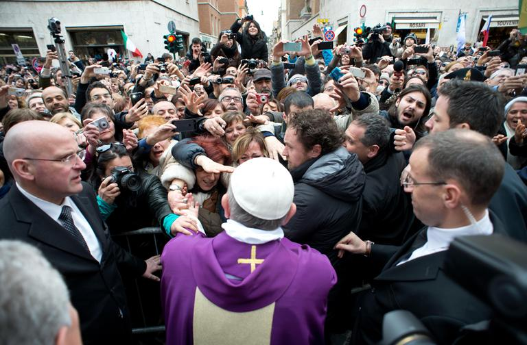 In this photo provided by the Vatican paper L'Osservatore Romano, Pope Francis greets faithful after making an impromptu appearance from a side gate of the Vatican, Sunday, March 17, 2013. (L'Osservatore Romano/AP)