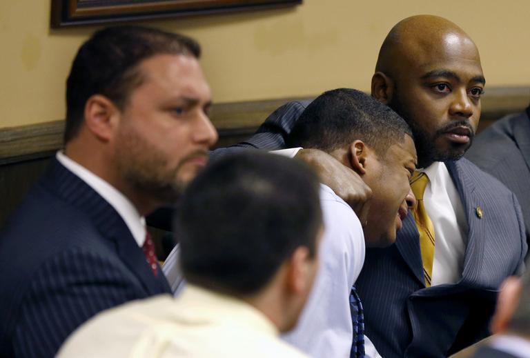 Defense attorney Walter Madison, right, holds his client, 16-year-old Ma'Lik Richmond, second from right, while defense attorney Adam Nemann, left, sits with his client Trent Mays, foreground, 17, as Judge Thomas Lipps pronounces them both delinquent on rape and other charges after their trial in juvenile court in Steubenville, Ohio, Sunday, March 17, 2013. (Keith Srakocic/AP)