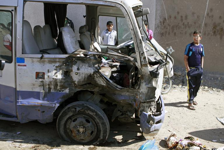 Children inspect a bus destroyed in a car bomb attack in the Shiite stronghold of Sadr City, Baghdad, Iraq, Tuesday, March 19, 2013. (Karim Kadim/AP)