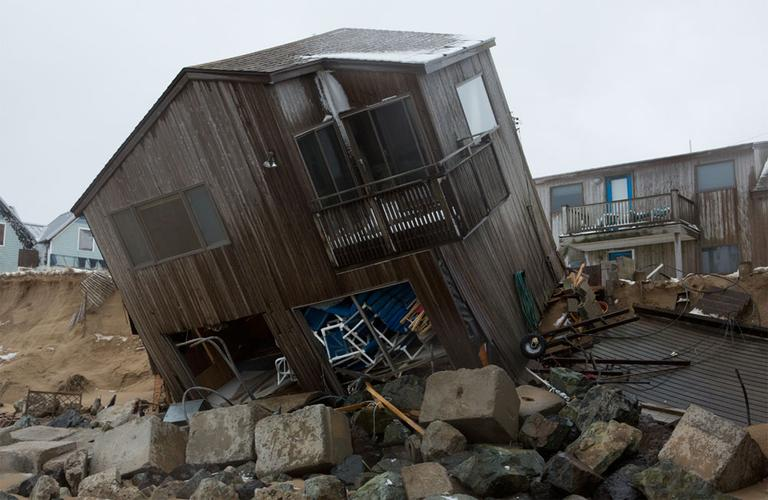 The winter storm that battered New England's coastline last week ripped two Plum Island homes off their foundation and left them partially collapsed into the ocean. (Jesse Costa/WBUR)