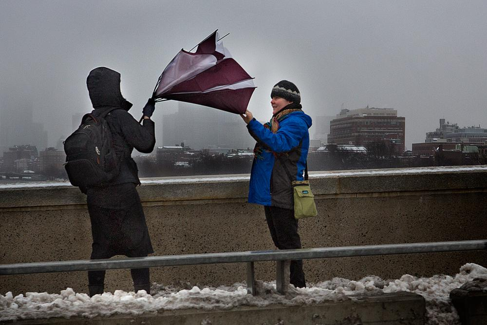 A woman's umbrella is turned inside-out Tuesday morning on BU Bridge. (Jesse Costa/WBUR)