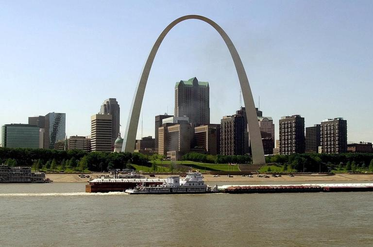 The St. Louis skyline with the Gateway Arch is shown in the background as a tug boat tows barges along the Mississippi River, May 2000. (James A. Finley/AP)
