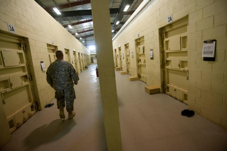 This Sept. 27, 2010, file photo reviewed by the U.S. military, shows a U.S. military guard walking a corridor between detainee cells at the Parwan detention facility. (David Guttenfelder/AP File)