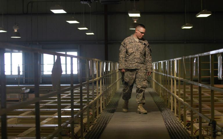 In this March 23, 2011 file photo, a U.S. military guard watches over detainee cells inside the Parwan detention facility near Bagram, north of Kabul, in Afghanistan. (Dar Yasin/AP File)