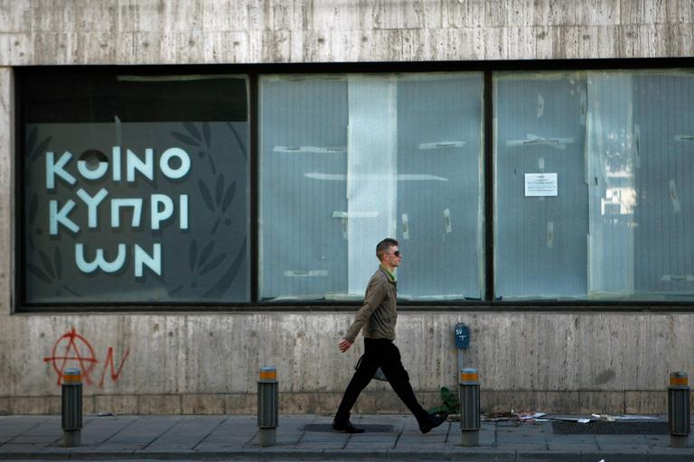 A man passes an empty closed branch of Bank of Cyprus in central capital Nicosia, Cyprus, Sunday, March 24, 2013. (Petros Karadjias/AP)