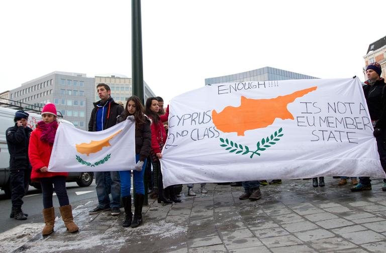People hold a banner with the flag of Cyprus on it during a demonstration outside of an emergency eurogroup meeting in Brussels on Sunday, March 24, 2013. (Virginia Mayo/AP)