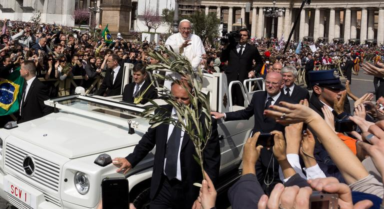 Pope Francis waves at a cheering crowd as he wades through St. Peter's Square at the Vatican on Sunday. (Domenico Stinellis/AP)