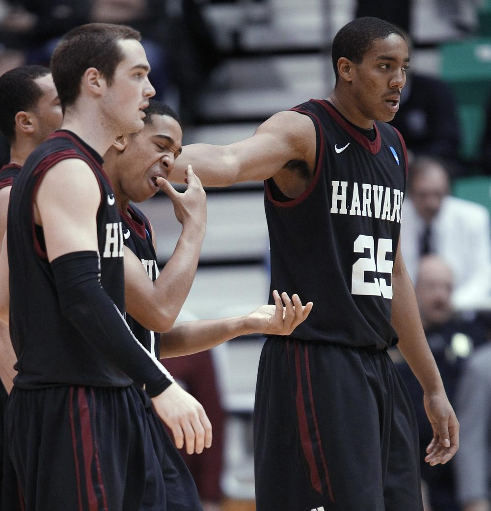 Harvard's Christian Webster, right, and Larent Rivard help Siyani Chambers, who had part of a tooth knocked out, off the court in the second half against Arizona. (AP Photo/George Frey)