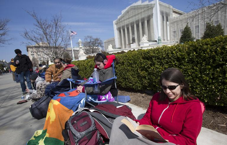 In this photo taken Saturday, March 23, 2013, Jessica Skrebes of Washington reads while waiting in line with others outside of the U.S. Supreme Court in Washington, in anticipation of the week's Supreme Court hearings on gay marriage. (Jacquelyn Martin/AP)
