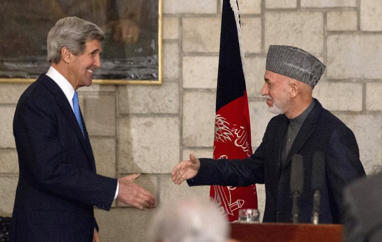 Secretary of State John Kerry reaches to shakes hands with Afghan President Hamid Karzai at the end of their joint news conference at the Presidential Palace in Kabul, Monday, March 25, 2013. (Jason Reed/AP Pool)