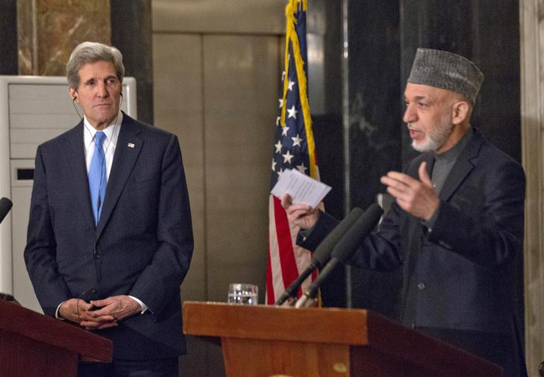 Secretary of State John Kerry listens as Afghan President Hamid Karzai speaks during their joint news conference at the presidential palace in Kabul. (Jason Reed/AP Pool)