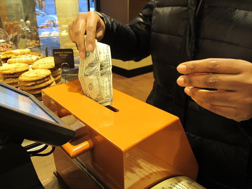 A customer inserts cash into a donation box to pay for her order at Panera Cares in Boston. (Kevin Sullivan/Here & Now)
